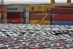 File - In this Thursday, May 16, 2019, file photo, cars for export and import are stored in front of containers at the port in Bremerhaven, Germany. The global economic rebound from the pandemic has picked up speed but remains uneven across countries and faces multiple headwinds including the lack of vaccines in poorer nations. That could lead to new virus variants and more stop-and-go lockdowns, the Organization for Economic Cooperation and Development, OECD said in its latest forecast. (AP Photo/Martin Meissner, File)