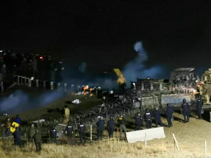FILE - In this Nov. 20, 2016, file photo, provided by Morton County Sheriff's Department, law enforcement and protesters clash near the site of the Dakota Access oil pipeline in Cannon Ball, N.D. Law enforcement officials in North Dakota say they aren't to blame for a severe arm injury a New York City woman suffered during the incident. They're asking a federal judge to throw out a lawsuit that Sophia Wilansky filed seeking millions of dollars in damages for alleged excessive force, assault, negligence, emotional distress and defamation. (Morton County Sheriff's Department via AP, File)