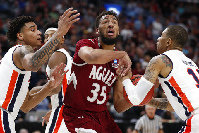 Auburn's forward Chuma Okeke, left, and guard Samir Doughty (10) defend against New Mexico State forward Johnny McCants (35) in the first half during a first round men's college basketball game in the NCAA Tournament, Thursday, March 21, 2019, in Salt Lake City. (AP Photo/Jeff Swinger)