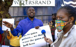 People protest against Coronavirus trials in Africa, outside the University of the Witwatersrand in Johannesburg, South Africa, Wednesday, July 1, 2020.  A protest against Africa's first COVID-19 vaccine trial is underway as experts note a worrying level of resistance and misinformation around testing on the continent.  (AP Photo/Themba Hadebe)