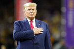 President Donald Trump listens to the national anthem before the NCAA College Football Playoff national championship game championship game between LSU and Clemson Monday, Jan. 13, 2020, in New Orleans. (AP Photo/David J. Phillip)