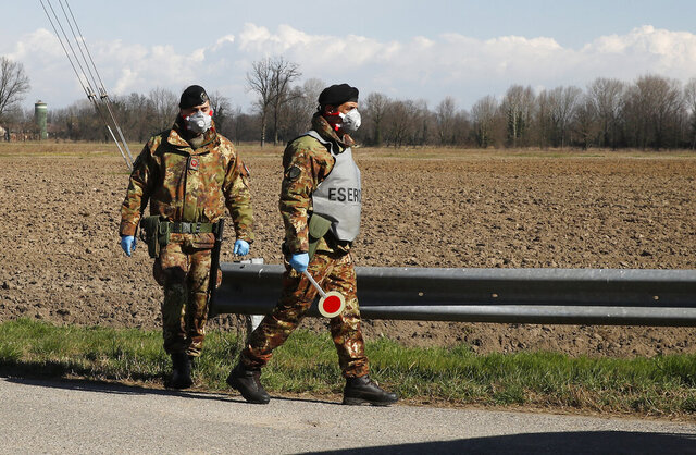 Italian Army soldiers check transit to and from the cordoned areas in Turano Lodigiano, Italy, Wednesday, Feb. 26, 2020. The viral outbreak that began in China and has infected more than 80,000 people globally, so far caused 374 cases and 12 deaths in Italy. (AP Photo/Antonio Calanni)