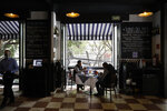 Diners sit at a table in front of open doors on the second story of Argentine grill Quebracho, in the Cuauhtemoc neighborhood of Mexico City, Monday, Jan. 11, 2021. More than three weeks into Mexico City's second pandemic shutdown some restaurateurs worried about their ability to survive ignored official warnings and opened limited seating Monday under the slogan,