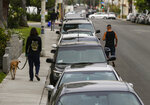 In this Friday, May 22, 2020, a line of vehicles are parked in Los Angeles. The coronavirus hasn't been kind to car owners. With more people than ever staying home to lessen the spread of COVID-19, their sedans, pickup trucks and SUVs are parked unattended on the streets, making them easy targets for opportunistic thieves.  (AP Photo/Damian Dovarganes)