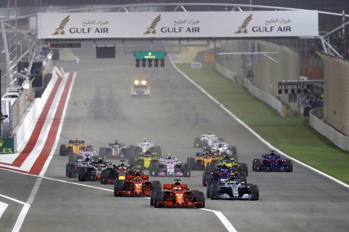 FILE- In this April 8, 2018 file photo, Ferrari driver Sebastian Vettel of Germany, center, leads at the start and followed by Mercedes driver Valtteri Bottas of Finland, right and Ferrari driver Kimi Raikkonen of Finland, left, during the Bahrain Formula One Grand Prix, at the Formula One Bahrain International Circuit in Sakhir, Bahrain. The Formula One race this month in Bahrain will be run without spectators over fears about the new coronavirus, the island kingdom announced Sunday, March 8, 2020, as Mideast stock markets fell sharply amid plummeting demand for crude oil and OPEC's inability to agree on a production cut. (AP Photo/Luca Bruno, File)