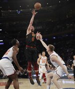 Cleveland Cavaliers' Kevin Love (0) shoots over New York Knicks' Henry Ellenson, right, and Noah Vonleh, left, during the second half of an NBA basketball game Thursday, Feb. 28, 2019, in New York. The Cavaliers won 125-118. (AP Photo/Frank Franklin II)