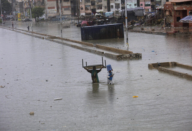 Women carry a cot and a bucket as they wade through a flooded road during a heavy monsoon rainfall, in Karachi, Pakistan, Tuesday, Aug. 25, 2020. Three days of monsoon rains have killed dozens of people and damaged hundreds of homes across Pakistan, the country's national disaster management agency said Tuesday, as another spell of heavy rain lashed the port city of Karachi. (AP Photo/Fareed Khan)
