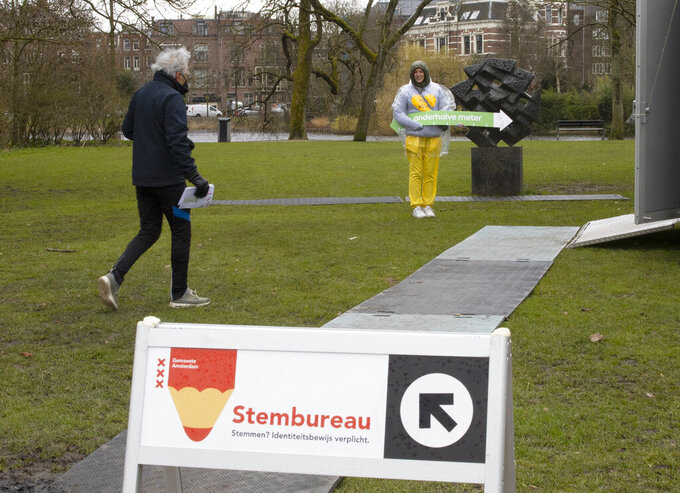 """A voter walks towards a volunteer at a polling station wearing a sweatshirt emblazoned with a yellow heart and the text """"keep your distance"""" while holding an arrow measuring out the 1.5-meter social distance in Amsterdam, Netherlands, Monday, March 15, 2021. Polling stations opened across the Netherlands early Monday in a general election that has been spread over three days to allow people to vote safely during the coronavirus pandemic. (AP Photo/Peter Dejong)"""
