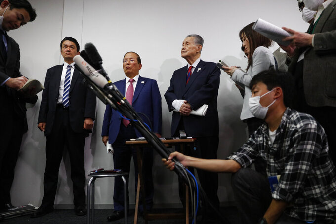 The Tokyo 2020 Organizing Committee's Toshiro Muto, center left, and Yoshiro Mori, center right, listen to questions from the media during a news conference in Tokyo, Wednesday, March 4, 2020. The Olympic Games are under threat from a spreading virus from China that has reached the pandemic stage. (AP Photo/Jae C. Hong)
