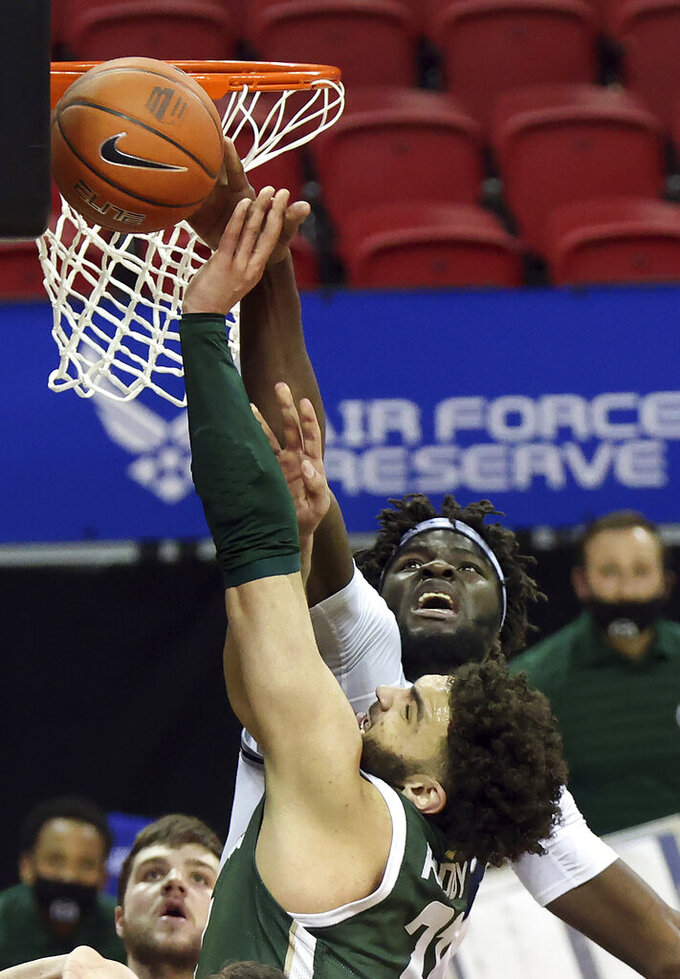 Utah State center Neemias Queta (23) blocks a shot from Colorado State guard David Roddy (21) during the second half of an NCAA college basketball game in the semifinal round of the Mountain West Conference men's tournament Friday, March 12, 2021, in Las Vegas. (AP Photo/Isaac Brekken)