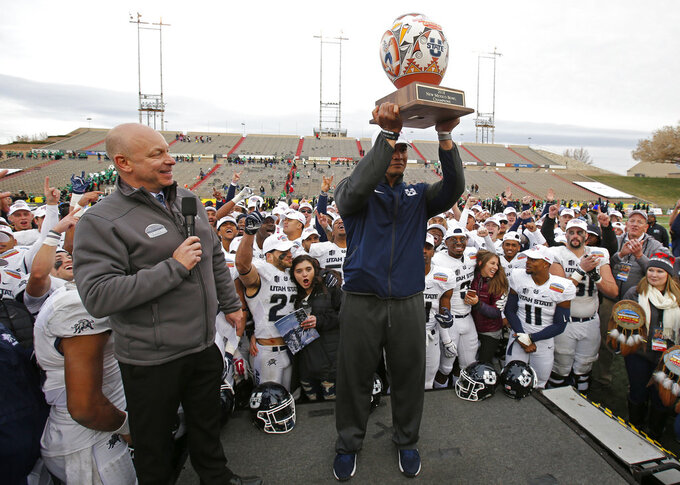 Utah State interim head coach Frank Maile lifts the trophy after his team's victory over North Texas in the New Mexico Bowl NCAA college football game in Albuquerque, N.M., Saturday, Dec. 15, 2018. (AP Photo/Andres Leighton)
