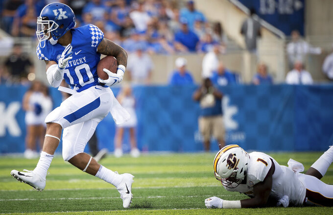 Kentucky running back Asim Rose (10) beats the tackle of Central Michigan defensive back Alonzo McCoy (1) to run for a 55-yard touchdown in the first quarter of an NCAA college football game in Lexington, Ky., Saturday, Sept. 1, 2018. (AP Photo/Bryan Woolston)
