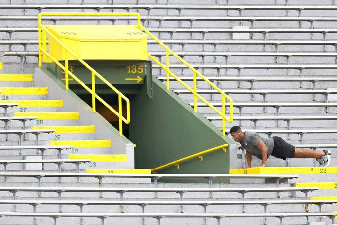 Green Bay Packers coaching assistant Ruvell Martin does push ups in the stands before an NFL football game against the Pittsburgh Steelers Sunday, Oct. 3, 2021, in Green Bay, Wis. (AP Photo/Matt Ludtke)