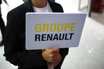 A hostess holds a sign of French automaker Renault Group to show the way for the Renault shareholders general meeting in Paris, France, Wednesday, June 12, 2019. (AP Photo/Francois Mori)