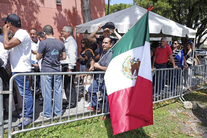 A fan holds a Mexican flag while he waits in line outside of the Miami-Dade County Auditorium during a public funeral for the late Mexican singer Jose Jose, Sunday, October 6, 2019 in Miami. (AP Photo/Gaston De Cardenas)