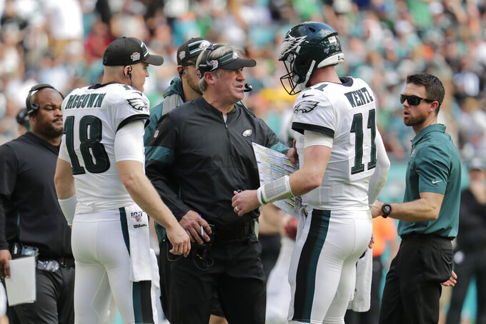 Philadelphia Eagles head coach Doug Pederson talks to quarterback Carson Wentz (11) on the sidelines, during the first half at an NFL football game, Sunday, Dec. 1, 2019, in Miami Gardens, Fla. (AP Photo/Lynne Sladky)