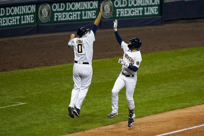Milwaukee Brewers' Ryan Braun celebrates his three-run home run with third base coach Ed Sedar during the eighth inning of a baseball game against the Kansas City Royals Saturday, Sept. 19, 2020, in Milwaukee. (AP Photo/Morry Gash)