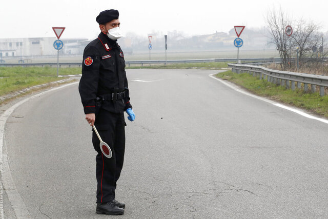Carabinieri (Italian paramilitary police) officer checks enter or leave the cordoned area in Casalpusterlengo, Italy, Tuesday, Feb. 25, 2020. A dozen Italian towns saw daily life disrupted after the deaths of two people infected with the virus from China and a pair of case clusters without direct links to the outbreak abroad. A rapid spike in infections prompted authorities in the northern Lombardy and Veneto regions to close schools, businesses and restaurants and to cancel sporting events and Masses. (AP Photo/Antonio Calanni)