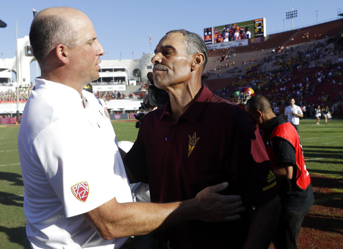 Arizona State head coach Herm Edwards, right, shakes hands with Southern California head coach Clay Helton after Arizona State's 38-35 win during an NCAA college football game Saturday, Oct. 27, 2018, in Los Angeles. (AP Photo/Marcio Jose Sanchez)
