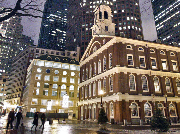 FILE - In this Feb. 22, 2007 file photo, people walk past Faneuil Hall, right, one of the sites on Boston's Freedom Trail in Boston. Black artist Steve Locke said Tuesday, July 16, 2019, that he's withdrawing his proposal for a slave memorial in front of Faneuil Hall after the NAACP objected. (AP Photo/Michael Dwyer, File)