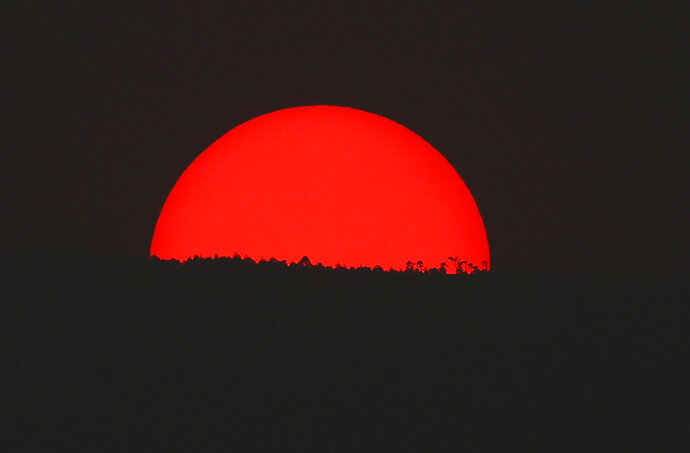 Tinted blood red by a thick cloud of smoke and pollution, the sun sets on the mountains above Mexico City, Monday, May 13, 2019. Mexico City's government has warned residents to remain indoors as forest and brush fires carpeted the metropolis in a smoky haze that has alarmed even many of those accustomed to living with air pollution. (AP Photo/Marco Ugarte)