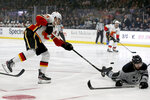 Los Angeles Kings defenseman Drew Doughty, right, blocks a shot by Calgary Flames center Sean Monahan, left, during the first period of an NHL hockey game in Los Angeles, Saturday, Oct. 19, 2019. (AP Photo/Alex Gallardo)