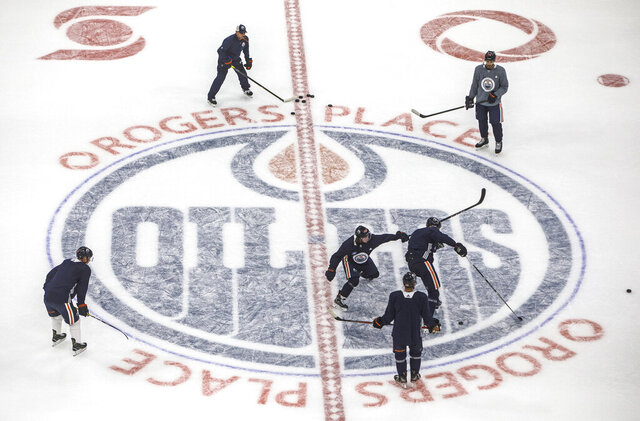 "FILE - Edmonton Oilers players take part in drills during NHL hockey training camp in Edmonton, Alberta, in this Monday, July 13, 2020, file photo. The Canadian government has given its OK to start NHL training camps, citing ""national interest grounds."" It has issued an exemption to the mandatory 14-day quarantine period for NHL players and team staff to return to the country. (Jason Franson/The Canadian Press via AP)"