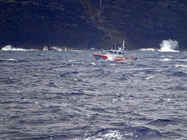 FILE - In this Dec. 27, 2019 file photo released by the U.S. Coast Guard, a coast guard vessel searches along the Na Pali Coast on the Hawaiian island of Kauai after a tour helicopter disappeared with seven people aboard. Officials say the pilot in the Hawaii tourism helicopter crash that killed him and six passengers previously lost his professional license for a year due to drug use. The Garden Island reported the Federal Aviation Administration revoked the professional certificates of Safari Helicopters pilot Paul Matero in June 2010. (Lt. j.g. Daniel Winter/U.S. Coast Guard via AP,File)