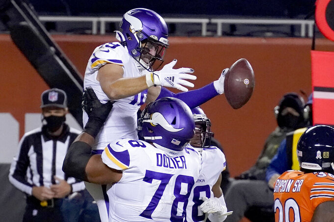 Minnesota Vikings wide receiver Adam Thielen is congratulated by teammate Dakota Dozier (78) after catching a touchdown pass during the second half of an NFL football game against the Chicago Bears Monday, Nov. 16, 2020, in Chicago. (AP Photo/Charles Rex Arbogast)