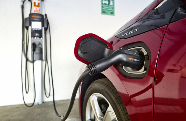 FILE - This Oct. 17, 2018 photo shows a Chevrolet Volt hybrid car charging at a ChargePoint charging station at a parking garage in Los Angeles.  The country, and the world, will need thousands more for drivers to accept vehicles that are powered by batteries alone. But automakers and charging companies are struggling to raise the numbers now because they're investing before demand arrives. With more than 40 fully electric vehicles on the market in the U.S. or coming within the next three years, however, auto and charging company executives say the demand is on the way.(AP Photo/Richard Vogel, File)