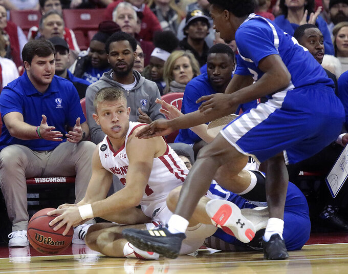 Wisconsin guard Brad Davison, left, looks to pass during a during the first half of an NCAA college basketball game against Eastern Illinois in Madison, Wis., Friday, Nov. 8, 2019. (John Hart/Wisconsin State Journal via AP)