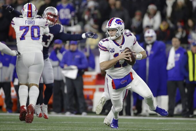 Buffalo Bills quarterback Josh Allen, right, rolls out to pass against the New England Patriots in the first half of an NFL football game, Saturday, Dec. 21, 2019, in Foxborough, Mass. (AP Photo/Elise Amendola)