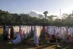 Indonesian Muslims offer Eid al-Fitr prayers to mark the end of the holy fasting month of Ramadan as Mount Merapi is seen in the background at Sleman, Yogyakarta, Indonesia, Friday, June 15, 2018. (AP Photo/Slamet Riyadi)