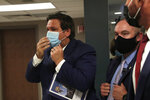 Florida Gov. Ron DeSantis, left, adjusts his face mask as he leaves a news conference at the old Pan American Hospital during the coronavirus pandemic, Tuesday, July 7, 2020, in Miami. (AP Photo/Lynne Sladky)