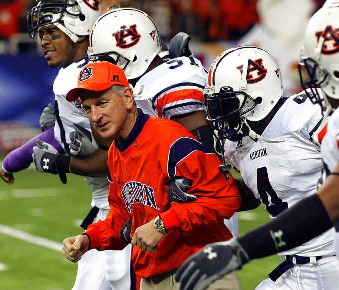 FILE - In this Dec. 4, 2004, file photo, Auburn coach Tommy Tuberville links arms with his players as the run onto the field prior to the Southeastern Conference football championship game against Tennessee,  at the Georgia Dome in Atlanta. Players from left: Mayo Sowell (57), Travis Williams (51) and Junior Rosegreen. In 2004, more controversy ensued when USC, Oklahoma, Auburn, Utah and Boise State all went through the regular season undefeated. The BCS national title matchup, which in those days was partially decided by the AP poll, went to USC and Oklahoma while the other three were left out. (AP Photo/Ric Feld, File)