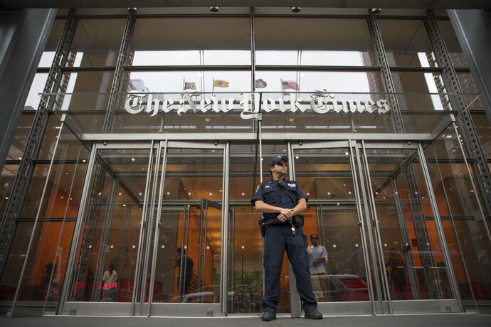 FILE- In this June 28, 2018, file photo, a police officer stands guard outside The New York Times building in New York. The New York Times Co. reports financial results Wednesday, Nov. 6, 2019. (AP Photo/Mary Altaffer, File)
