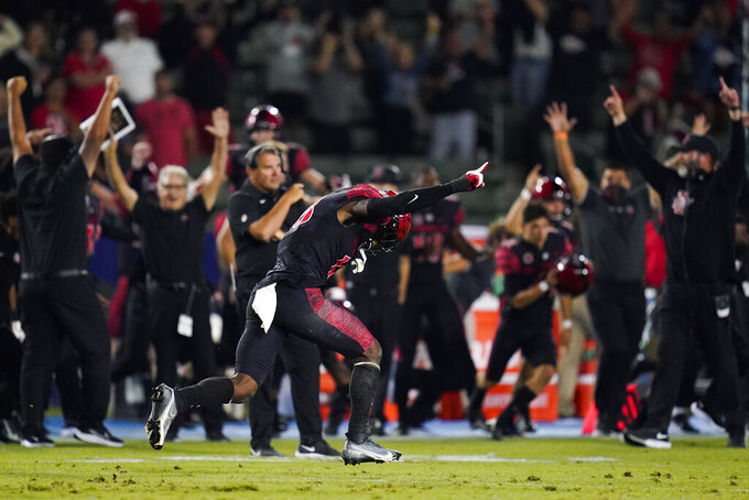 San Diego State players and staff celebrate a 33-31 win in triple overtime against Utah in an NCAA college football game Saturday, Sept. 18, 2021, in Carson, Calif. (AP Photo/Ashley Landis)