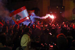 Anti-government demonstrators hold flares and Lebanese flags, during a protest on a road leading to the parliament building in Beirut, Lebanon, Thursday, Jan. 16, 2020. Lebanese protesters Thursday decried security forces' use of violence during rallies over the past two days, including attacks on journalists and the detention of over 100 people. (AP Photo/Bilal Hussein)