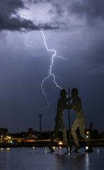 In this Aug. 9, 2018 photo a thunderbolt strikes behind the sculpture Molecule Man in Berlin. (Paul Zinken/dpa via AP)