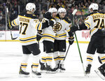 Boston Bruins' Patrice Bergeron (37), Brad Marchand (63), Torey Krug (47) and Jake DeBrusk (74) celebrate a gaol against the Minnesota Wild by Marchand during the second period of an NHL hockey game Saturday, Feb. 1, 2020, in St. Paul, Minn. (AP Photo/Hannah Foslien)