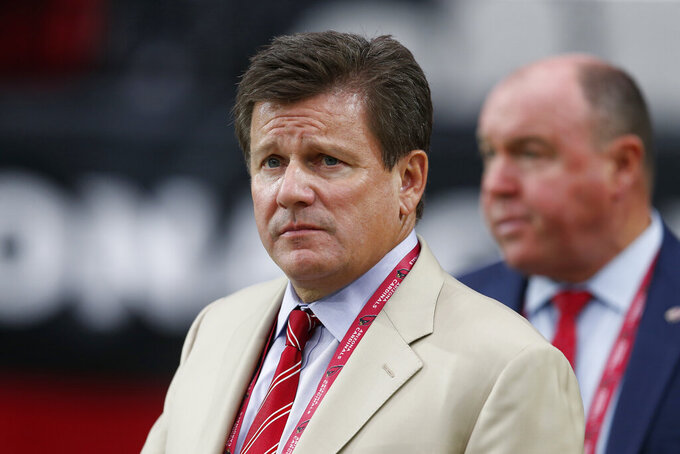 FILE - In this Aug. 15, 2019, file photo, Arizona Cardinals owner Michael Bidwill waits for the team's NFL preseason football game against the Oakland Raiders in Glendale, Ariz. The Cardinals say owner Bidwill has been released from a Rhode Island hospital after testing positive for COVID-19 last week. The team revealed on Friday, July 9, that the 55-year-old Bidwill was in the hospital with the virus. (AP Photo/Ralph Freso, File)