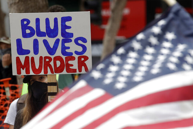 A woman holds a sign at a protest over the Memorial Day death of George Floyd, a handcuffed black man in police custody in Minneapolis, in San Francisco, Saturday, May 30, 2020. (AP Photo/Jeff Chiu)