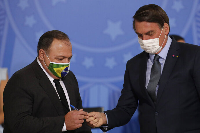 Brazil's President Jair Bolsonaro, wearing a mask to curb the spread of COVID-19, hands a pen to Health Minister Gen. Eduardo Pazuelo, left, at Planalto Presidential Palace, in Brasilia, Brazil, Wednesday, Sept. 16, 2020. After almost four months overseeing the COVID-19 response as interim health minister, Gen. Eduardo Pazuello will finally be made a full minister. (AP Photo/Eraldo Peres)