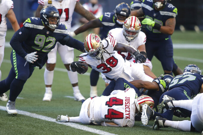 San Francisco 49ers running back JaMycal Hasty (38) gets the ball over the line for a touchdown as Seattle Seahawks defensive tackle Bryan Mone (92) moves in during the first half of an NFL football game, Sunday, Nov. 1, 2020, in Seattle. (AP Photo/Scott Eklund)