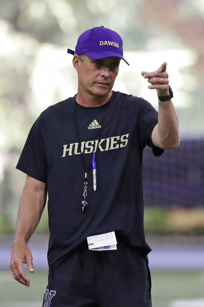 FILE - In this Aug. 5, 2019, file photo, Washington head coach Chris Petersen looks on during an NCAA football practice in Seattle. In his tenure at Washington, Chris Petersen has faced situations where the Huskies lose a significant chunk of talent to the next level, only to replenish and continue what's been an upward trend during his first five seasons in charge.  This season will test whether the Huskies can simply continue to reload. (AP Photo/Elaine Thompson, File)