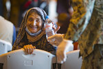 A woman from Afghanistan smiles after being given a bottle of water after disembarking from a U.S. airforce plane at the Naval Station in Rota, southern Spain, Tuesday Aug. 31, 2021. The United States completed its withdrawal from Afghanistan late Monday, ending America's longest war.(AP Photo/ Marcos Moreno)