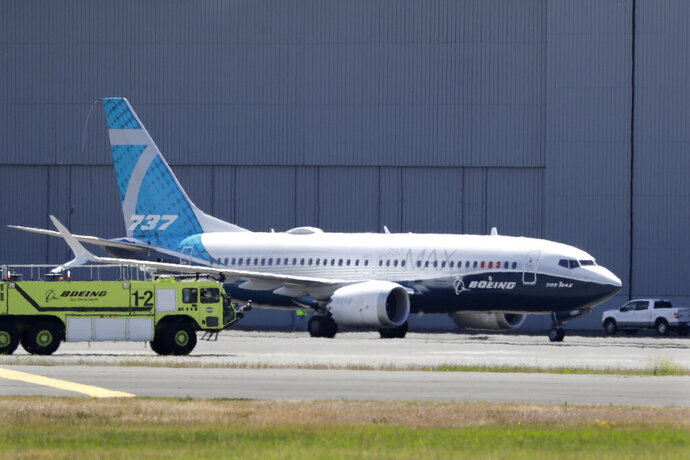 FILE - In this Monday, June 29, 2020, file photo, A Boeing 737 MAX jet taxis after landing at Boeing Field following a test flight in Seattle. Boeing will pay $2.5 billion to settle a criminal charge related to its troubled 737 Max jetliner. The Justice Department announced the settlement Thursday, Jan. 7, 2021 nearly two years after the second of two crashes that killed 346 people in all.  (AP Photo/Elaine Thompson)