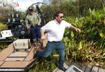 FILE - In this Sept. 12, 2018 file photo, then Republican candidate for Florida Governor Ron DeSantis, gets off an airboat with Gladesman and former Florida Fish and Wildlife Conservation commissioner Ron Bergeron after a tour of the Florida Everglades in Fort Lauderdale, Fla.  In his first 10 months in office, Florida Gov. Ron DeSantis has appointed a science officer, established a czar on climate change and pushed action against red tide and algae blooms.  (AP Photo/Wilfredo Lee)