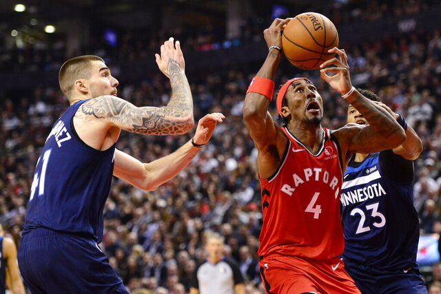 Toronto Raptors forward Rondae Hollis-Jefferson (4) grabs a rebound between Minnesota Timberwolves forward Juan Hernangomez (41) and guard Jarrett Culver (23) during first half NBA basketball action in Toronto, Monday, Feb. 10, 2020. (Frank Gunn/The Canadian Press via AP)