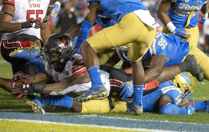 Utah running back Zack Moss, top, dives for a touchdown over UCLA linebacker Krys Barnes, bottom, during the second half of an NCAA college football game Friday, Oct. 26, 2018, in Pasadena, Calif. (AP Photo/Kyusung Gong)